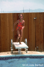 Photograph of a girl jumping into a swimming pool
