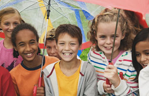A group of kids crowded together holding umbrellas.