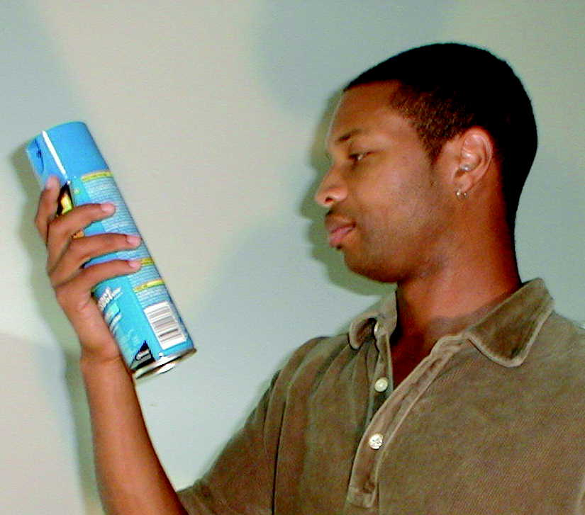 Man reading the label of a household aerosol product.
