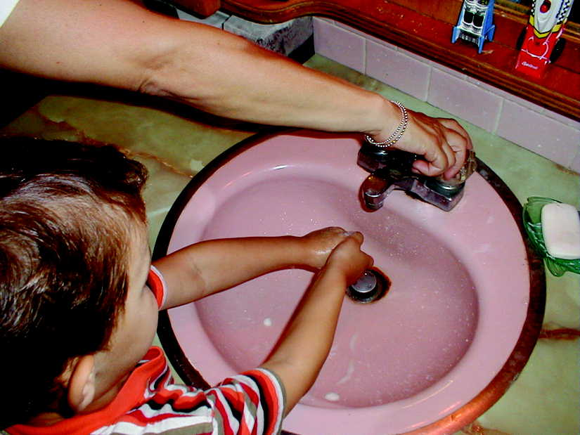 Mom and son at the bathroom sink making sure he washs his hands properly.