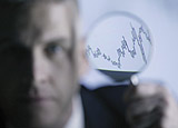 Man with magnifying glass viewing line graph