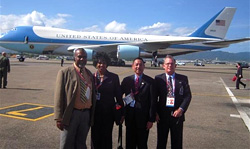 Photo of Ramesh Lutchmedial, Director General of Trinidad and Tobago Civil Aviation Authority; Loretta McNeir, TSA Representative; and Transportation Security Inspectors Kevin Yap-Sam and Thomas Finneman standing near Air Force One.