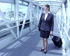 Business woman pulling luggage bag through airport