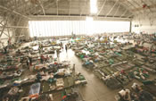 cots and people inside a large airplan hangar