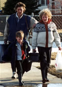 Woman with her children fleeing on foot with bags and suitcases along a sidewalk