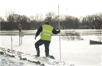 Man measuring water and ice levels along riverbank.