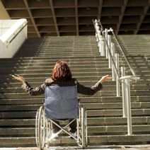 Woman in wheelchair looks up at a long stairway entrance.