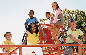 A group of kids climbing on a jungle gym.