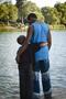 adult hugging child in lake