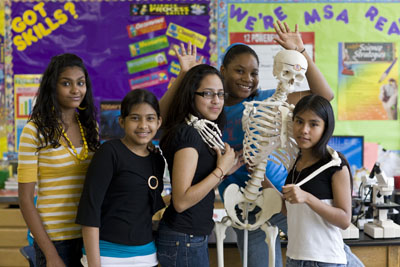 Female students posing with skeleton in a classroom