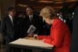 U.S. Secretary of State Hillary Rodham Clinton signs the November 26, 2008 memorial book at the Taj Mahal Palace Hotel in Mumbai, July 18, 2009