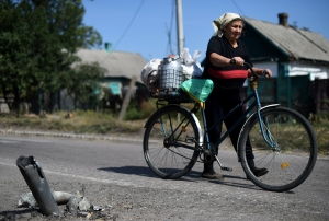 A woman pushes her bicycle past a non-exploded rocket in Ilovaisk, 50km southeast of Donetsk, 4 September. Photo: Getty